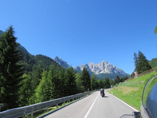 route avec un motard sous un ciel bleu en montagne