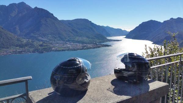 deux casques de moto devant le lac de Côme