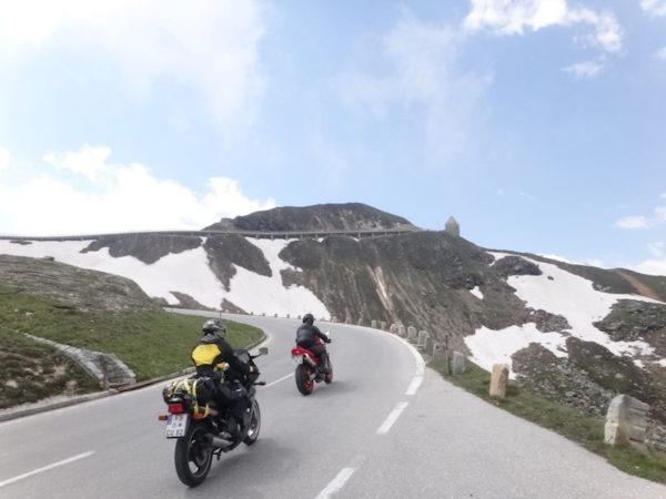 Route de montagne avec de la neige au loin et des moto dessus