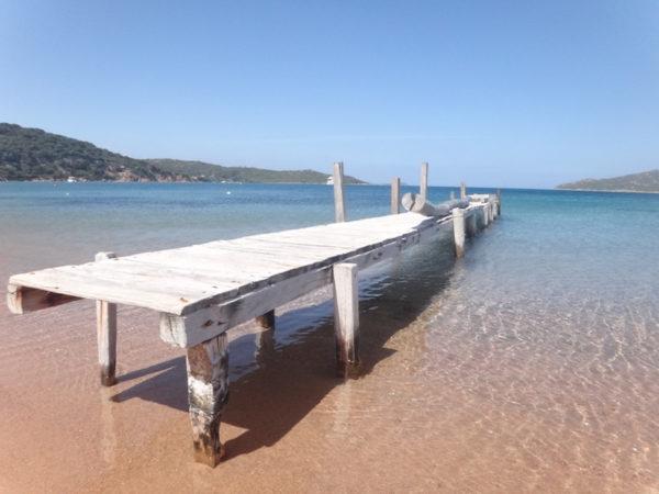 Ponton sur une plage de Corse en voyage moto