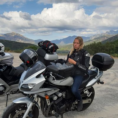 Motarde sur sa moto devant un paysage de montage