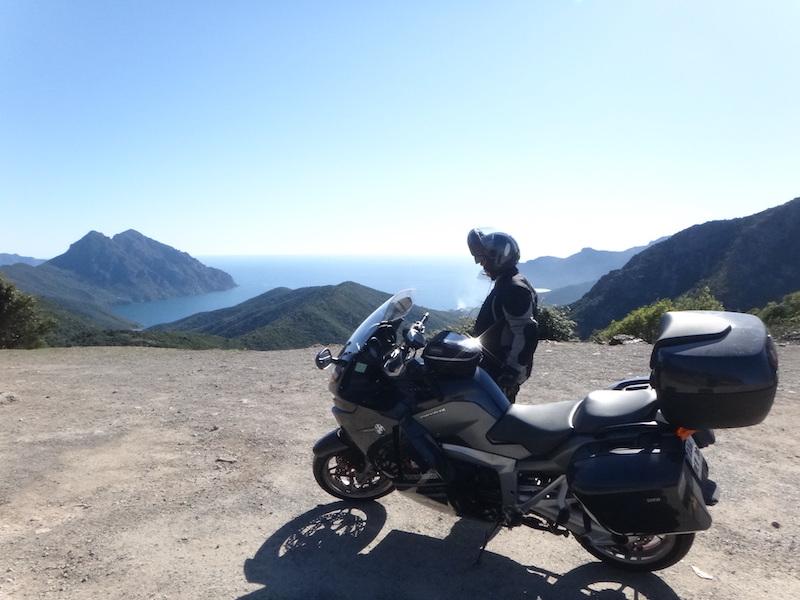 motard et sa moto qui admire la vue du col routier corse de palmarella