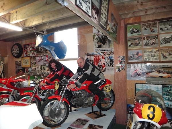 chantal et pierre chevauchent des motos dans le musee moto de Peter Murray sur l'île de man